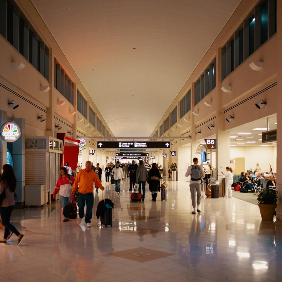 People walking along airport corridor.